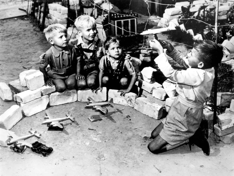 """OPERATION VITTLES"" (Berlin Airlift)  Berlin youngsters who live near the Tempelhof Air Force Base, where the U.S. Air Force transport planes unload their airlift supplies, play at a game called ""Luftbrucke"" (air bridge).  They use model American planes which are sold in German toy shops throughout the western sector of Berlin. (Wikipedia)"